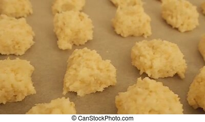Making coconut macaroons - Raw coconut macaroons on a baking...
