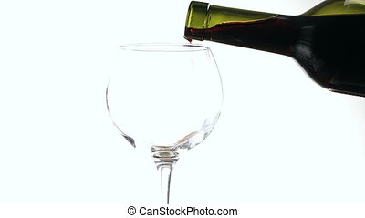 Pouring red wine into a glass on white background. - Pouring...
