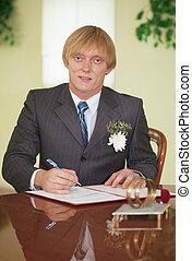 Groom puts signature on registration document - The groom...