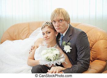 Future husband and wife on leather sofa - The future husband...