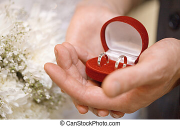 Hands of groom and bride hold casket with rings - Hands of...