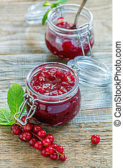 Jars with homemade jam and red currant.
