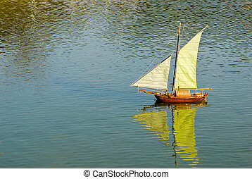 Handmade remote control sailboat on lake - sailboat on the...
