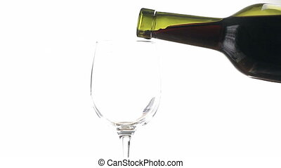 Pouring red wine into a glass on white background.