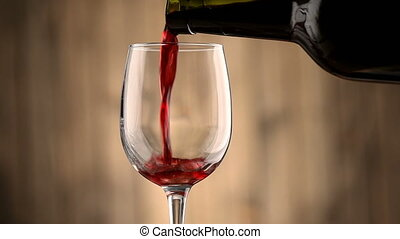 Pouring red wine into a glass. - Pouring red wine into a...