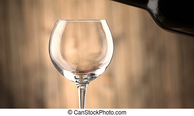 Pouring red wine into a glass.