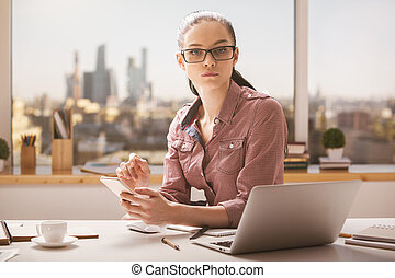 Portrait of businesswoman at workplace - Portrait of...