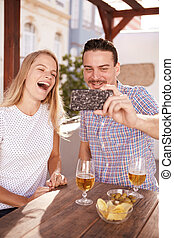 Laughing couple taking a happy selfie while sitting at a...