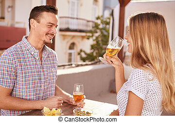 Happily smiling couple having some drinks while sitting...