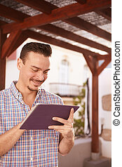 Cool dark haired guy smiling at tablet - Cool dark haired...