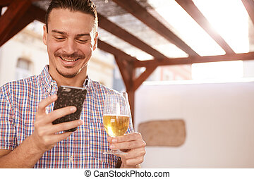 Good looking guy grinning at cellphone - Good looking guy...