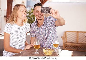 Handsome young couple taking a selfie with big open mouth...
