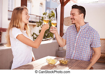 Couple raising and clinking their glasses - Happily laughing...