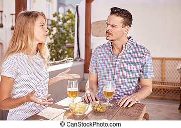 Cute couple in a deep discussion - Cute couple sitting with...