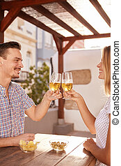 Good looking couple raising their glasses together - Good...