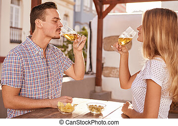 Charming young couple sharing some drinks sitting across...
