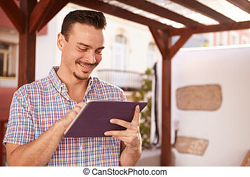 Dark haired guy looking at his tablet - Handsome guy with...