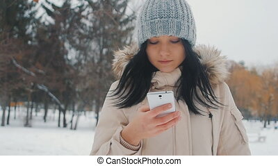 Portrait of Young cute woman in winter park uses smartphone