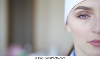 Close-up shot of female medical worker looking into camera