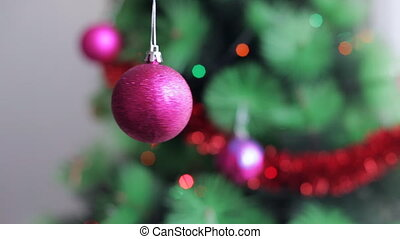 Pink Christmas ball on defocused New Year tree background