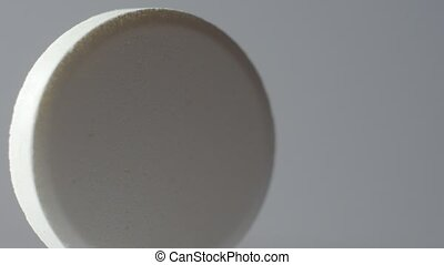 White pill rotate on a white background. Macro. - White pill...
