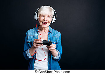 Positive aged woman playing video games - Involved in it....