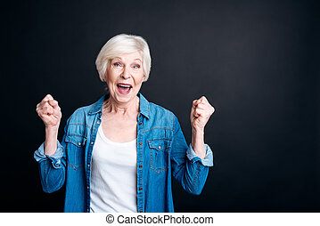 Delighted elderly woman standing on black background - True...
