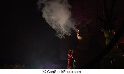 Beautiful young woman smoking hookah in dark shisha bar