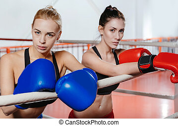 Two sexy athletic girls leaning on the ropes - We are...