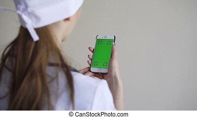 Female doctor showing smart phone with green screen