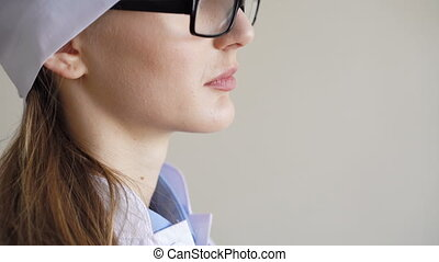 Portrait of a young adult female doctor with glasses, looking at the window