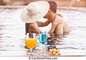 Romantic Asian couple kissing in the swimming pool with...