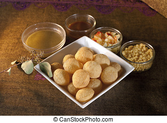 Golgappa or pani puri, a chat item with accompaniments in...