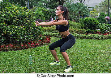 Young female athlete doing squat exercises outdoors in park....