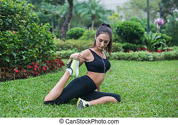 Fit young woman dressed in black sportswear doing stretching...
