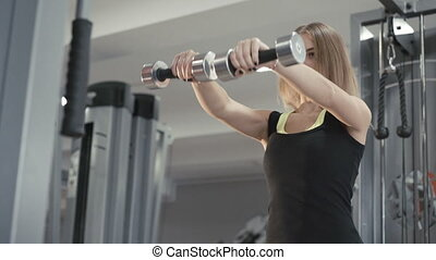 Strong girl working out with dumb-bell for delta muscles in...