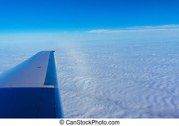 Wing of airplane flying above the clouds in the sky sky...