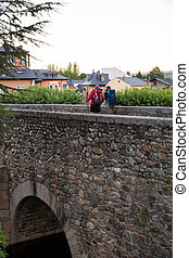 Pilgrimns on the stone bridge along the way of St. James -...