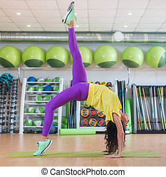 Beautiful young fit woman in sportswear doing yoga pose in...