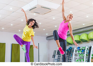 Two young sporty women exercising in fitness studio,...
