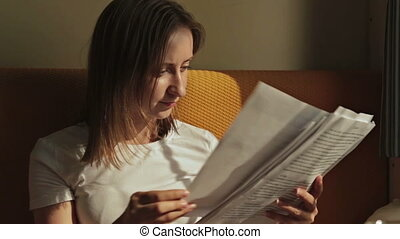Woman reading a documents in cabin of cruise ship. Sunset...