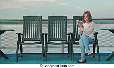 woman with pc digital tablet sitting on deck of cruise ship at sunrise