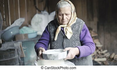 Wrinkled old woman sifting flour in barn in 4K.