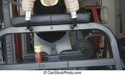 Front look of girl working out with simulator for legs and...