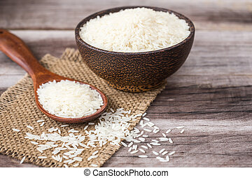 White Thai jasmine rice on wooden plank background
