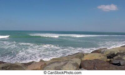 Deserted ocean stony coastline with foaming waves