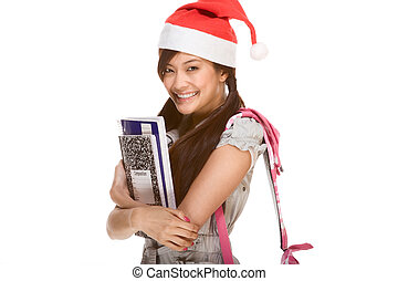 Asian schoolgirl wearing red Santa Claus hat with backpack...