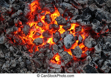 Charred and fire in dark - Charred wood and bright flames on...