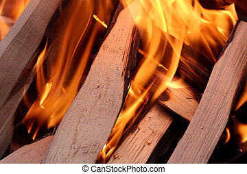 Fire on dark background - Charred wood and bright flames on...