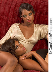 Two ethnic sexy women on sofa in retro clothes - Two dark...